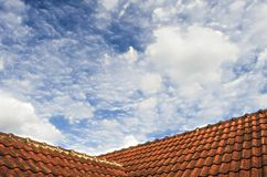 Tiled Roof with Fluffy Cloud Blue Sky Royalty Free Stock Image