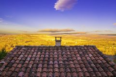 A tiled roof of a house in a village with wide fields behind the house Stock Images