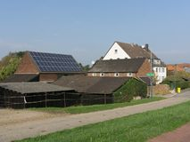 Tiled roofs of rural stone houses with a solar battery in the European suburbs stock image