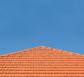 Tiled Rooftop on Blue Sky. An orange-tiled rooftop against a clear blue sky Stock Photo