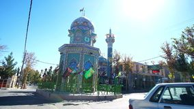 The tiled Shrine with a clock tower in the middle of the square in Rayen. RAYEN, IRAN - OCTOBER 16, 2017: The beautiful tiled Shrine with a clock tower in the stock footage
