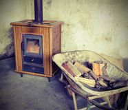 Tiled stove and wheelbarrow full of firewood with vintage effect Royalty Free Stock Photo