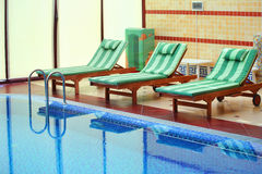 Tiled swimming pool with bed-chairs. On the side Royalty Free Stock Photos
