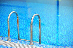 Tiled swimming pool with blue water. And ladder Stock Image