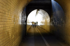 Tiled Tunnel. A long tunnel with tiled walls, and people disappearing into the light royalty free stock images