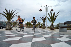 A Tiled Walkway Kids Riding Bicycles  Stock Photos