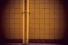 Tiled wall with pipe Stock Photo
