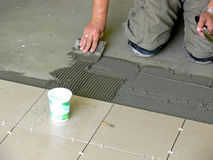 Tiler. Closeup of kneeing tiler putting concrete and tiles on the floor Stock Image