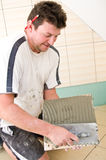 Tiler. A tiler at work, putting new tiles on the wall Royalty Free Stock Image