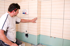 Tiler. At work, putting new tiles in bathroom Stock Photography