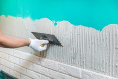 Tiler applying tile adhesive on the wall Royalty Free Stock Photography