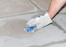 Tiler cleaning tiles after filling up joints Royalty Free Stock Images