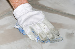Tiler cleaning tiles after filling up joints Royalty Free Stock Image
