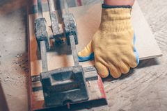 Tiler com um cortador de telha à mão fotografia de stock royalty free