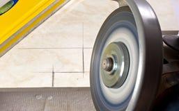 Tiler cutting tile angle grinder Royalty Free Stock Images