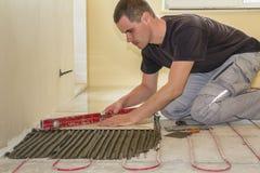 Tiler för ung arbetare som installerar keramiska tegelplattor genom att använda spaken på cementgolv med att värma det röda tråds royaltyfria bilder