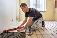 Tiler för ung arbetare som installerar keramiska tegelplattor genom att använda spaken på cementgolv med att värma det röda tråds royaltyfria foton