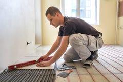 Tiler f?r ung arbetare som installerar keramiska tegelplattor genom att anv?nda spaken p? cementgolv med att v?rma det r?da tr?ds royaltyfri foto