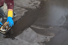Tiler grouting tiles. With dark gray Stock Images
