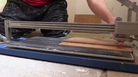 Tiler hands using tile cutter tool on floor. Left side slide stock video footage