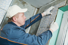 Tiler at indoor wall tiling renovation. Industrial tiler builder worker installing wall tile at repair renovation work Royalty Free Stock Photos