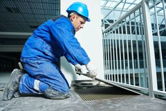 Tiler at industrial floor tiling renovation Royalty Free Stock Images