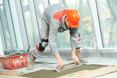Tiler at industrial floor tiling renovation work Stock Photography