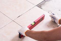 Tiler installing ceramic tiles. On a floor Royalty Free Stock Image