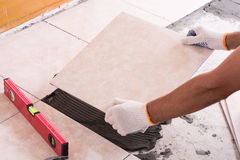 Tiler installing ceramic tiles. On a floor Stock Photography