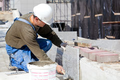 Tiler installing marble tiles Royalty Free Stock Photos
