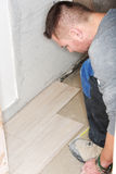 Tiler installs ceramic tiles Stock Photo