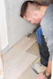 Tiler installs ceramic tiles Stock Photo