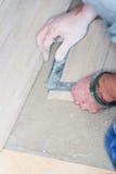 Tiler installs ceramic tiles Royalty Free Stock Image