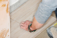 Tiler installs ceramic tiles Stock Images