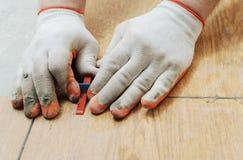Tiler& x27; la mano di s sta allineando le mattonelle Immagine Stock Libera da Diritti