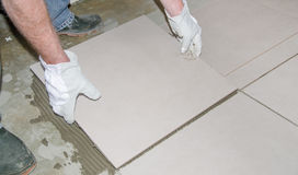 Tiler laying a new tile on the floor Royalty Free Stock Images