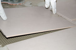 Tiler laying a new tile on the floor Stock Images