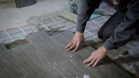 Tiler is lying tile on a floor, pressing down and regulating, installing plastic industrial crosses for fixing stock footage