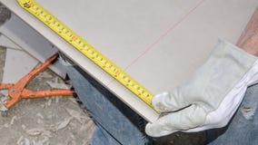Tiler measuring tile before cutting Royalty Free Stock Photo
