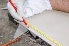 Tiler measuring tile before cutting Stock Image