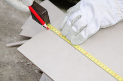 Tiler measuring tile before cutting Stock Photos