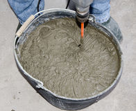 Tiler mixing tile adhesive with power drill in a bucket Stock Photography