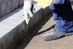 tiler processes the surface for laying the stone tiles on the steps in the repair of the office building. Royalty Free Stock Photo