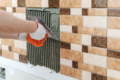 A tiler& x27;s hand is holding a notched trowel. Royalty Free Stock Photos