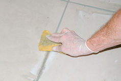 Tiler smoothing tile joints with a sponge Stock Photos