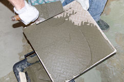 Tiler spreading tile adhesive on the back of a tile Stock Photo