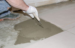 Tiler spreading tile adhesive on the floor Stock Photography