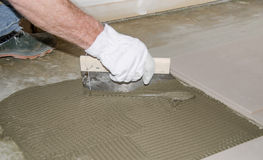 Tiler spreading tile adhesive on the floor Royalty Free Stock Photo