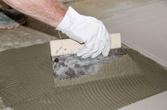 Tiler spreading tile adhesive on the floor Stock Image