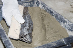 Tiler taking tile adhesive with a notched trowel Stock Images
